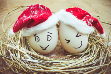 Happy eggs with painted faces in the nest for Christmas