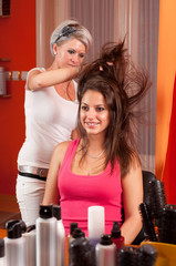 Hairdresser making hair of beautiful smiling teenage girl