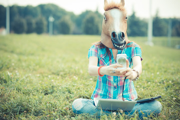 horse mask unreal hipster woman using technology