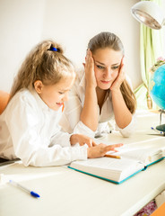 confused mother looking at daughters homework