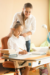 smiling woman looking at girl doing homework at bedroom
