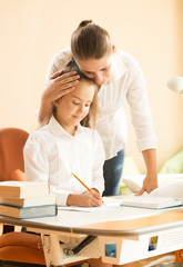 young mother praising daughter doing homework at desk