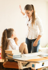angry mother hitting intimidated daughter