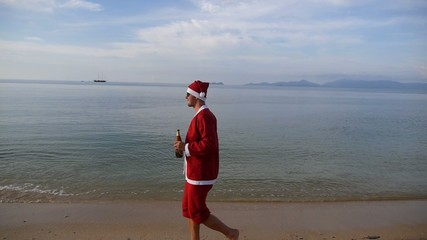 Happy Santa Claus Walking on Beach with Beer. Slow Motion.