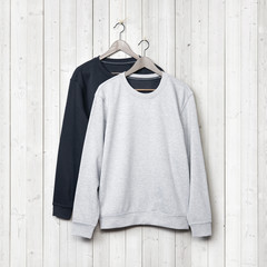 Sweaters on a white wood wall