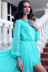 girl with dark hair in luxurious blue dress posing on stairs
