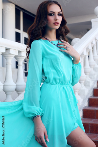 canvas print picture girl with dark hair in luxurious blue dress posing on stairs