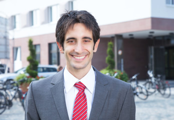 Erfolgreicher Geschäftsmann mit schwarzen Haaren vor dem Büro