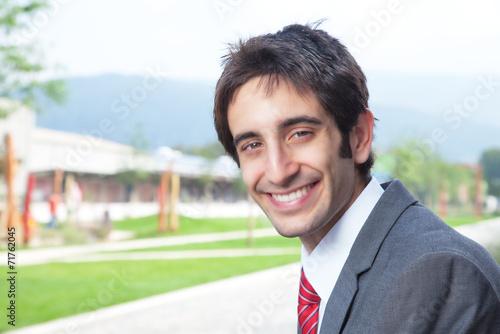 canvas print picture Lachender Geschäftsmann mit schwarzen Haaren im Park