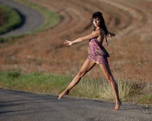 Danseuse traversant pieds nus une route de campagne