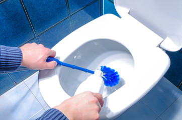 Man Cleaning Toilet Using Brush and Liquid Cleaner