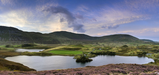 Stunning sunrise panorama landscape of heather with mountain lak
