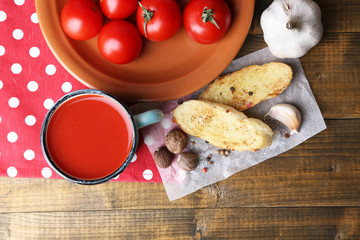 Homemade tomato juice in color mug, toasts and fresh tomatoes