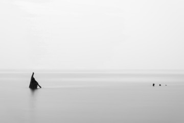 Minimalist landscape image of shipwreck ruin in sea black and wh