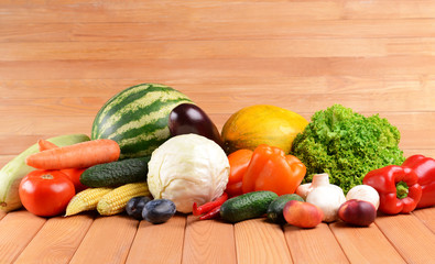 Fresh organic fruits and vegetables on wooden background