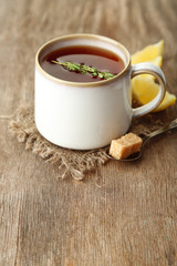 Cup of tasty herbal tea with thyme and lemon, on wooden table