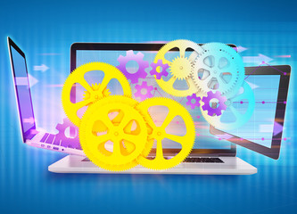 cogwheels, gear flying in front of laptop and a tablet.