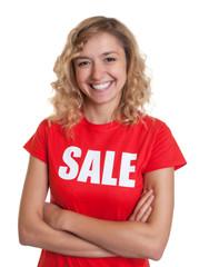 Lachende blonde Frau im Sale-Shirt