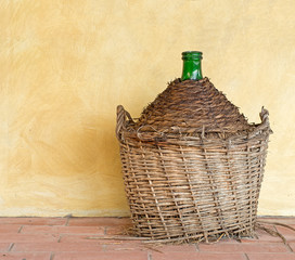 Old demijohn aka carboy for wine, wicker straw wrap, by house.