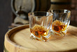 canvas print picture - Glasses of brandy in cellar with old barrels