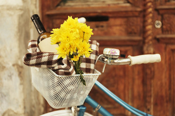 Old bicycle with flowers and checkered blanket in metal basket