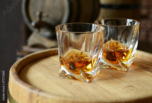 canvas print picture Glasses of brandy in cellar with old barrels