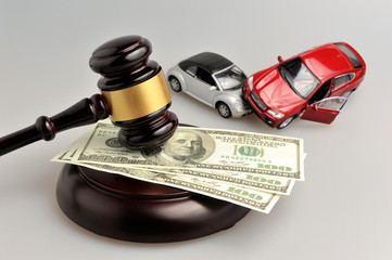 Hammer of judge with money and toy cars on gray