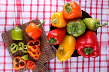 Pepper on plate and on cutting board on fabric background