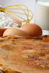 Milk, flour, whisk, pancakes and eggs