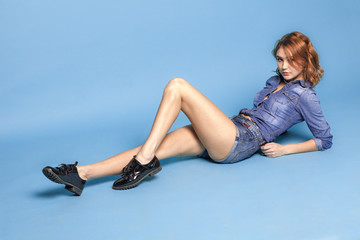 sexy adult girl in jeans wear sitting on blue background
