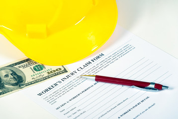 Worker injury claim hard hat with money and pen on white