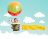 cheerful kid on hot air balloon with banner in the sky