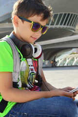 Teen boy with headphones and smartphone