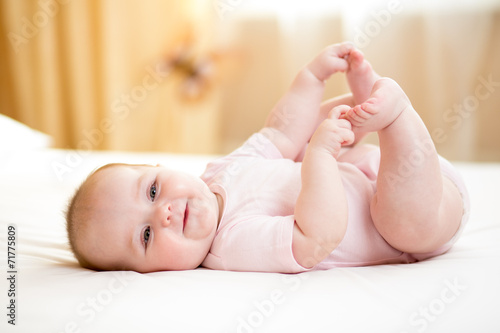 canvas print picture baby girl lying on white sheet and holding her legs