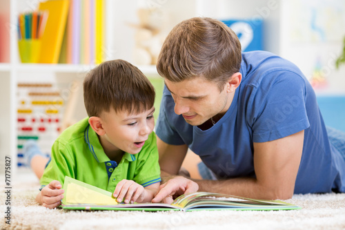 Leinwanddruck Bild kid boy and his father read a book on floor at home