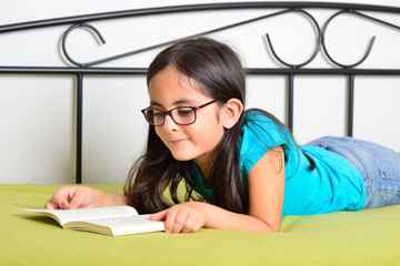 Little girl with glasses reading a book