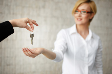 Happy owner passing keys from house in office