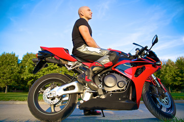 man sitting on red motorcycle