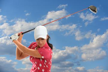 Female Golf Player Swinging Driver