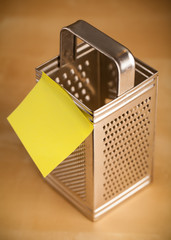 Empty post-it note sticked on grater