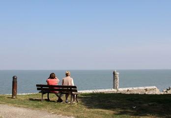 couple assis sur un banc et regardant la mer