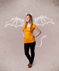 Young girl with devil horns and wings drawing