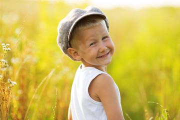 Happy smiling boy in a gray cap