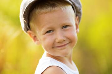 Happy smiling little boy in a cap