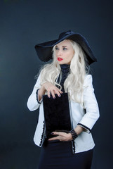 blonde woman with long hair in black hat holding a box and looks
