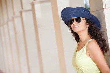 Portrait of a young smiling woman with hat and sunglasses