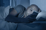 internet addict man awake at night in bed with mobile phone