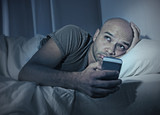 internet addict man at night in bed using smartphone poster