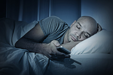 internet addict man at night in bed while using smartphone