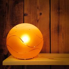 Cozy orange lamp on wooden shelf